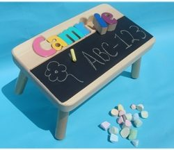 A kids stool with a name puzzle and chalkboard on it.